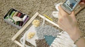 Een vrouw weeft op een weefgetouw een mooi die borduurwerk van garen wordt gemaakt, in een huisstudio, Foto's op de telefoon stock videobeelden