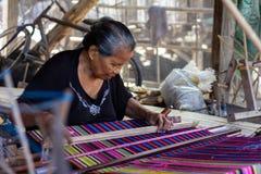 Een vrouw weeft traditionele kleurrijke stoffen van Flores Alle het weven processen gebruiken hand en traditioneel materiaal stock foto
