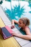 Een vrouw werkt aan de computer in de pool stock foto's