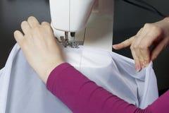Een vrouw werkt aan een naaimachine Zij naait de gordijnen op het venster Stock Afbeeldingen