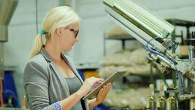 Een vrouw werkt met een tablet aan de wijnmakerij Een transportband met flessen wijn loopt rond het De voedselindustrie stock video