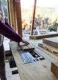 Een vrouw werkt in een timmerwerkworkshop stock foto