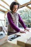 Een vrouw werkt in een timmerwerkworkshop stock afbeelding