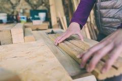 Een vrouw werkt in een timmerwerkworkshop stock foto's
