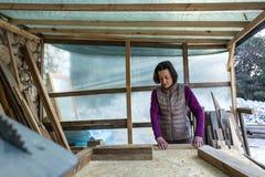 Een vrouw werkt in een timmerwerkworkshop royalty-vrije stock foto's
