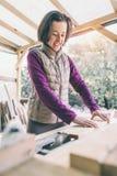 Een vrouw werkt in een timmerwerkworkshop stock fotografie