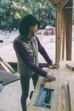 Een vrouw werkt in een timmerwerkworkshop royalty-vrije stock afbeeldingen