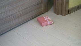 Een vrouw werpt een gift onder de deur stock footage
