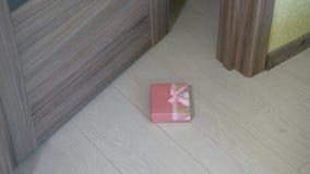 Een vrouw werpt een gift onder de deur stock videobeelden
