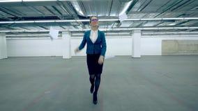 Een vrouw werpt weg documenten en begint om in een bureauruimte te dansen stock footage