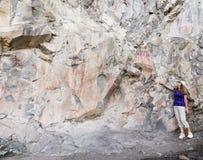 Een Vrouw wijst op Beeldschrifttekens in Gila Cliff Dwellings Stock Foto's
