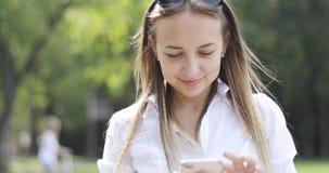 Een vrouw in een wit overhemd houdt een mobiele telefoon stock footage