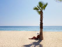 Een vrouw in witte hoedenzitting onder palm bij het strand stock afbeeldingen