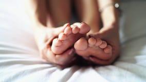Een vrouw wrijft de bodem van zijn vermoeide, pijnlijke voet stock video