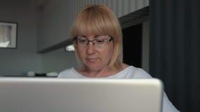 Een vrouw is een zakenman die het computerscherm bekijken Een meisje kleedt glazen op ogen dichte omhooggaand het werken in het b stock videobeelden