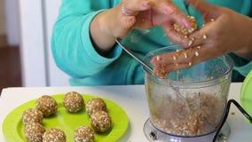 Een vrouw zet een bal van pinda's en andere ingrediënten op een plaat De spatie voor cake knalt stock video