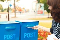 Een vrouw zet brieven in de brievenbus Royalty-vrije Stock Afbeeldingen