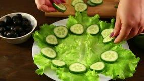 Een vrouw zet de gesneden komkommers op een witte plaat Close-up stock videobeelden