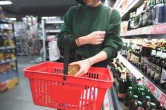 Een vrouw zet een fles alcohol in een rood boodschappenwagentje Het meisje zet een aankoop in de mand royalty-vrije stock foto