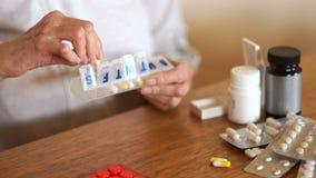 Een vrouw zet haar pillen in een plastic container De gepensioneerde neemt een dagelijkse dosis pillen en vitaminen stock videobeelden