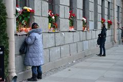 Een vrouw zet een kaars voor de slachtoffers van de terroristische aanslag op Stock Foto's