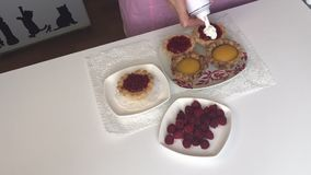 Een vrouw zet een lepel frambozenjam als het vullen in het gebakken voorvormen voor een cake stock video
