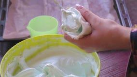 Een vrouw zet een mengsel van heemst in een gebakjezak stock videobeelden