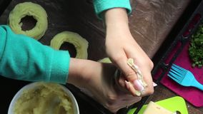 Een vrouw zet op een paddestoel vullende stukken van kaas Ringen die van fijngestampte aardappels, op het bakselblad liggen Naast stock videobeelden