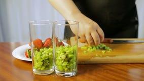 Een vrouw zet een stuk van kiwi in een cocktailglas stock video