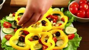 Een vrouw zet stukken zwarte olijven in een plaat met een plantaardige salade Close-up stock videobeelden