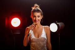 Een vrouw zingt een lied in de studio stock afbeelding