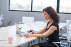 Een vrouw zit alleen in het bureau achter laptop binnen Royalty-vrije Stock Foto