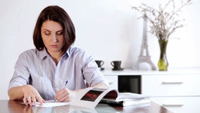 Een vrouw zit bij de lijst en schrijft iets met a ballpen stock video