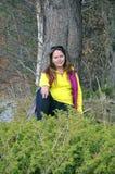 Een vrouw zit dichtbij een boom Stock Foto