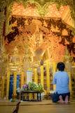Een vrouw zit om voor het gouden standbeeld van Boedha van Thailand tempel genoemd ?Wat Den Salee Sri Muang Gan Wat Ban Den ?te b stock afbeeldingen
