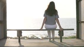 Een vrouw zit op een bank door het overzees en geniet van de mooie mening stock videobeelden