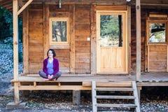 Een vrouw zit op de portiek van een oud blokhuis royalty-vrije stock foto
