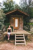 Een vrouw zit op de portiek van een oud blokhuis stock fotografie