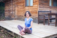 Een vrouw zit op de portiek van een oud blokhuis royalty-vrije stock afbeelding