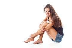 Een vrouw zit op de vloer Stock Afbeeldingen