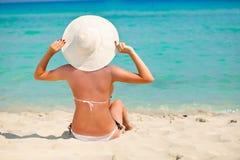 Een vrouw zit op een strand Stock Fotografie
