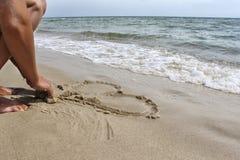 Een vrouw zit op het strand Stock Foto