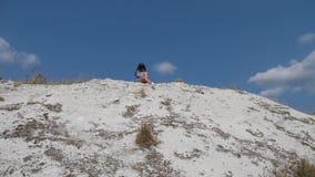 Een vrouw zit op een witte heuvel op een zonnige dag stock videobeelden
