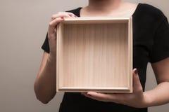 Een vrouw in zwarte T-shirt bevond zich brengend een houten doos stock afbeelding