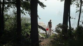 Een vrouw in een zwempak met een emmer in haar handen is op een houten pijler stock video