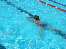 Een vrouw zwemt blauwe pool Stock Foto