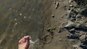 Een vrouwelijk been heft water bij een meerbank in op de zomer in slo-mo stock footage