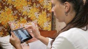 Een vrouwelijke arts bezoekt thuis een patiënt Het toont de resultaten van de Röntgenstraal op een tabletcomputer De man ligt  stock videobeelden