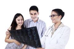 Een vrouwelijke arts die röntgenstraal tonen aan jong paar royalty-vrije stock foto's