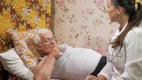 Een vrouwelijke arts geeft een pil van een huisziekte De man is drinkwater, liggend op de laag stock videobeelden